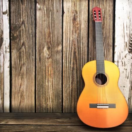 テキストまたはコピー領域のための部屋と木製のフェンスの広告に傾いている木製ギター 写真素材