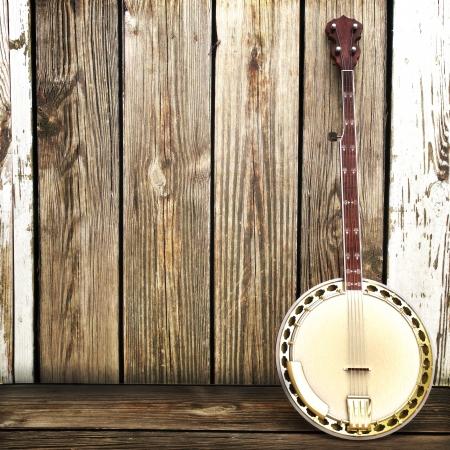 instrumentos musicales: Banjo apoyado en un anuncio de valla de madera con espacio para texto o espacio de la copia