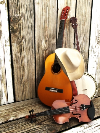 Country music background with stringed instruments  Guitar, banjo, violin and a cowboy hat leaning against a wood fence  Room for text or copy space  photo