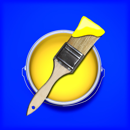 Yellow paint with wet paint brush over a contrasting colored blue background   photo