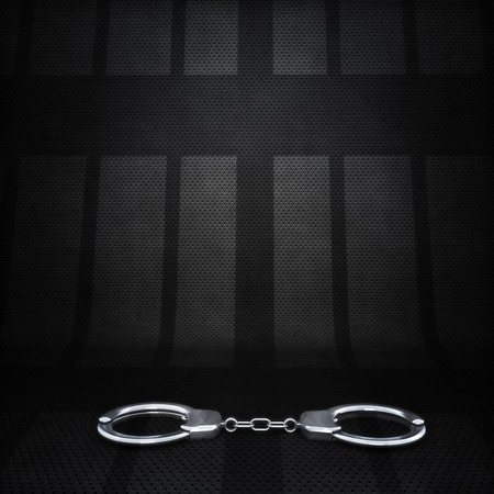 confinement: Jail scene background  Hand cuffs with silhouette of cell doors in the background  Stock Photo