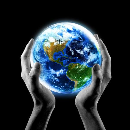 Tierra en sus manos, el concepto de ahorro de la Tierra, Manos que sostienen la Tierra con un fondo negro