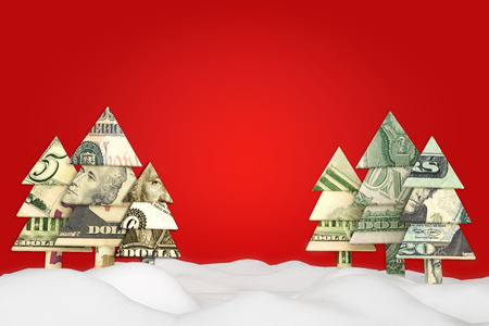 background: Holiday Christmas savings or sale advertisement. Origami money Christmas trees in the snow with a red background with room for text or copy space. Stock Photo