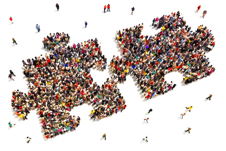 crowd: People putting the pieces together concept . Large group of people in the shape of two puzzle   pieces on a white background. Stock Photo