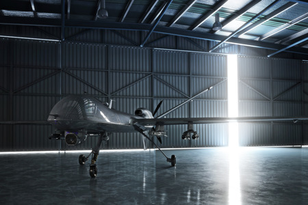 Awaiting flight. Lone drone U.A.V aircraft awaiting a military mission in a hanger.