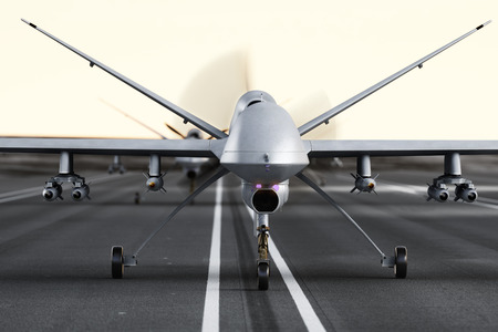 Military armed UAV drones preparing for takeoff on a runway Stock Photo