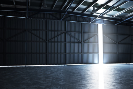 Empty building hanger with the door cracked open with room for text or copy space