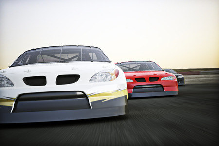 motorized sport: Front view of auto racing race cars racing on a track with motion blur. Stock Photo