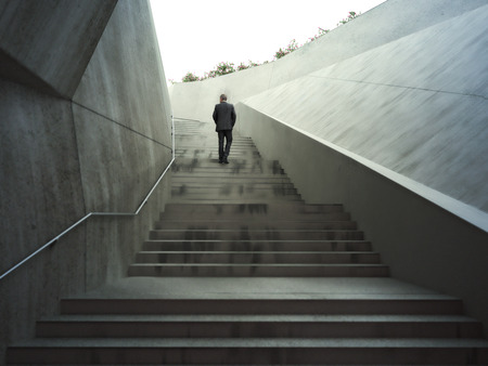 Ambitions concept with a businessman climbing up abstract stairs .Photo realistic 3d rendering.