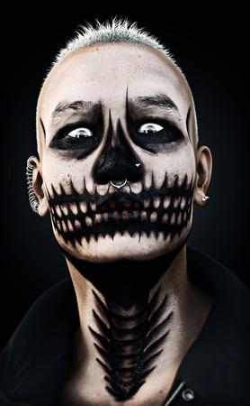 Retrato de un varón de miradas feroces de miedo con maquillaje de cráneo y perforaciones sobre un fondo negro. Las 3D