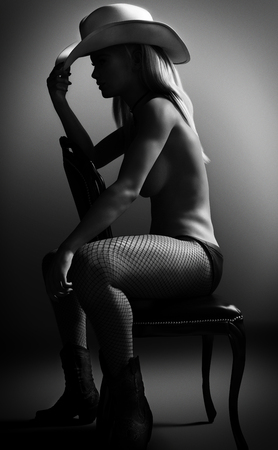 Sexy fit nude woman sitting on a chair wearing a cowboy hat with Studio lighting. Photo realistic 3d rendering scene in Black and White Lizenzfreie Bilder
