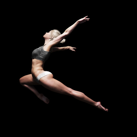 Athletic female leaping into the air with a black background. Symbolism of strength , power and beauty  . 3d rendering