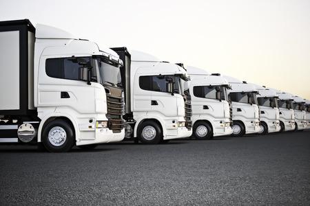 Flotte de camions de transport commerciaux blancs garés dans une rangée prêts pour la distribution commerciale. Rendu 3D avec espace pour le texte ou la copie d'espace publicitaire. Banque d'images