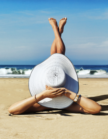 A day at the beach. Cute dainty female wearing a white two piece bikini and straw hat enjoying the sun at the beach. 3d rendering Stock Photo