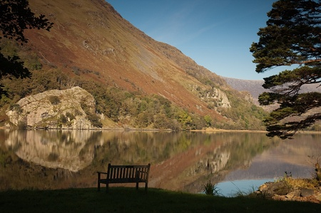 snowdonia: A bench by a lake on a still, autumn day in Snowdonia