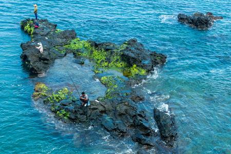 Senggigi - Fishermen on rock just offshore