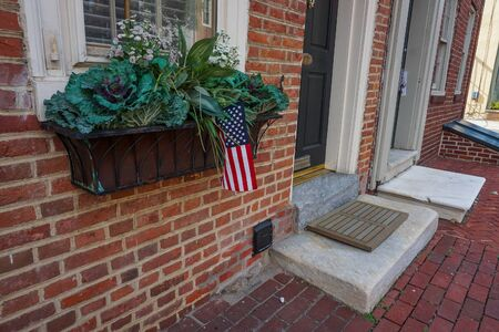 flowers and bush in front of city building with american flag Banco de Imagens