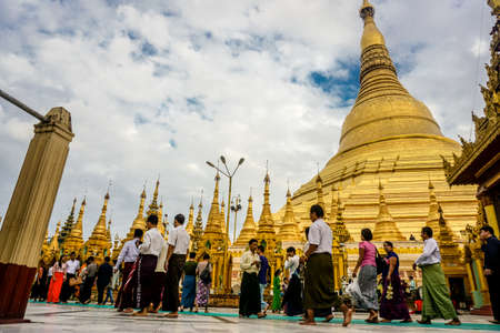 People walking around at Shwedagon Pagoda (officially named Shwedagon Zedi Daw) and also known as the Great Dagon Pagoda.  A  gilded stupa located in Yangon, Myanmar. Redactioneel