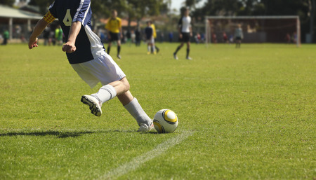 coaches: A young male soccer player takes a kick out from the goal square. Stock Photo