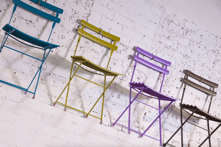 oblique: 4 colorful chairs hang on a white wall. Stock Photo