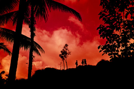 going up: Silhouette of 3 people going up a hill in the tropics. Stock Photo