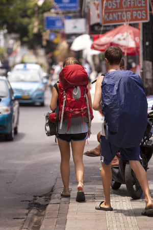 Two backpackers walk the streets of asia.