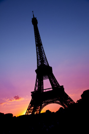 A silhouette of the Eiffel tower with a pink and blue sky.