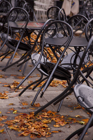 Black chairs and tables  amongst autumn leave at a closed European cafe..