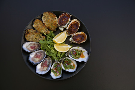 A plate of oysters 4 ways on a black background taken from above.