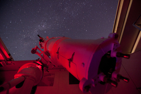 A large old telescope bathed in red light looking up at the night sky. Standard-Bild