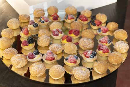 A platter of small berry tarts & puffs. Standard-Bild - 109023980