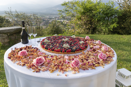 Large custard tart topped with berries, sparkling wine, rose petals.