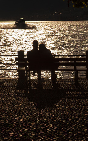 Silhouette of a couple sitting by Lake Como Standard-Bild