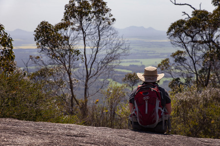 A Lone hiker looks out to distant ranges