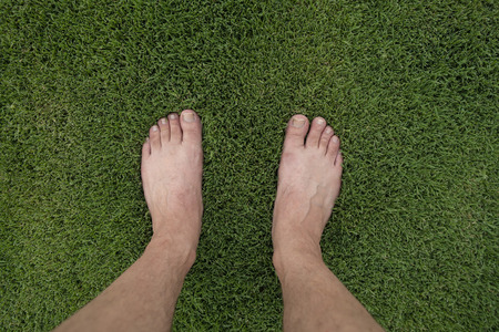 Feet stand on lush green lawn