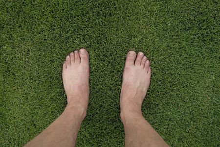 Feet stand on lush green lawn Standard-Bild - 116678709