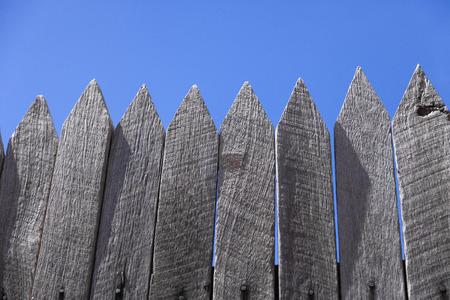 Grey picket fence against blue sky Standard-Bild