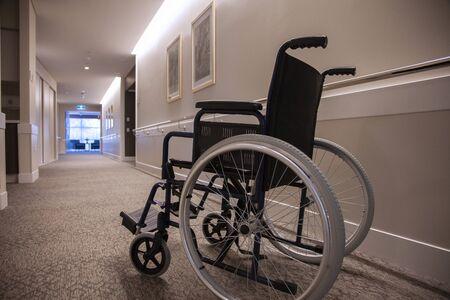 An empty wheelchair in an empty hallway.