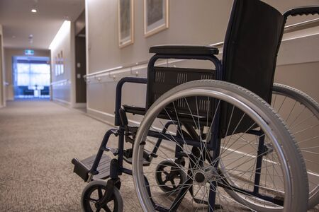 An empty wheelchair in an empty hallway, close.