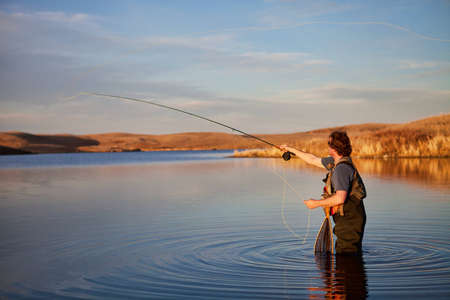 Fly fisherman casting in a lake in golden light. photo