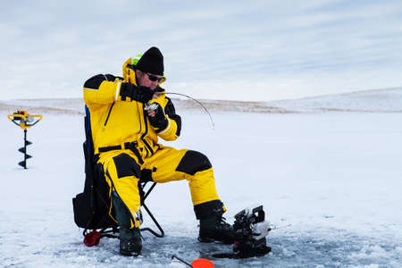 Ice fisherman with a fish on his line. photo
