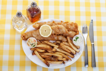 wedge: A traditional  plate of fish and chips on a yellow checkered tablecloth