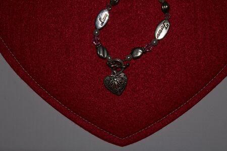 Valentines Day gift bracelet on red heart pad. Stok Fotoğraf