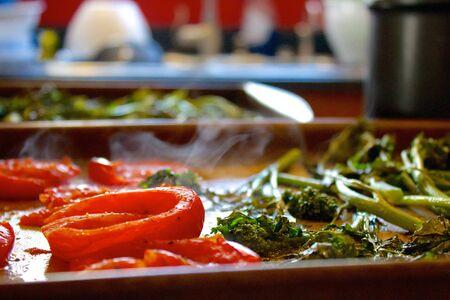 comida: Plano de uma assadeira com fumegantes tomates e brócolis Imagens