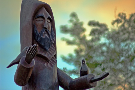 Cerro Gordo Park-Santa Fe, New Mexico. May, 2012. Statue of St. Francis de Assisi, wood carving sculpture during a colorful sunrise.