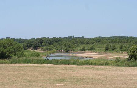 Il fiume rosso sullo sfondo di un campo. Archivio Fotografico - 5283119