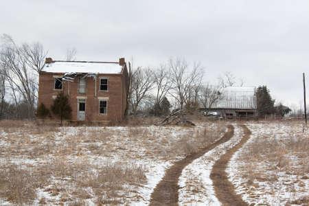 Abandoned farmhouse beside one lane road. Reklamní fotografie - 7235753