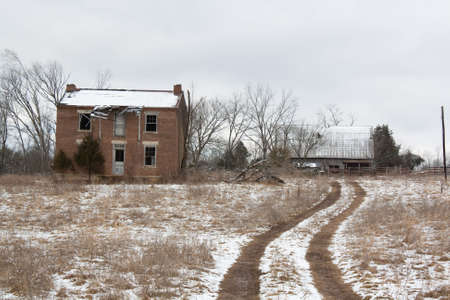 Abandoned farmhouse beside one lane road.