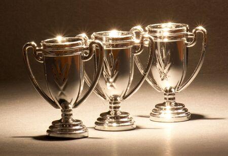Tre trofei lucidi in piedi in una riga. Archivio Fotografico - 8098145