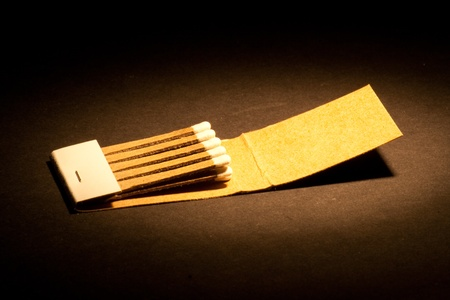 A book of matches lighted on a black background.